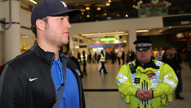 A police officer keeps an eye on Lions quarterback Matthew Stafford as he arrives at Gatwick Airport in Crawley, West Sussex, England on Tuesday.