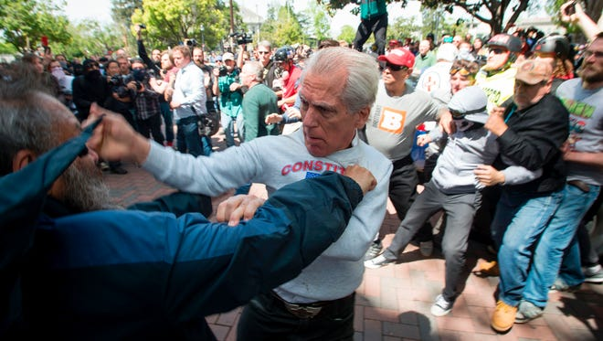 AFP_NL32T.jpg Two men fight during a pro-Trump rally in Berkeley, California on April 15, 2017.  Hundreds of people with opposing opinions on President Donald Trump threw stones, lit fires, tossed explosives and tear gas and attacked each other with makeshift weapons as police stood by. / AFP PHOTO / Josh EdelsonJOSH EDELSON/AFP/Getty Images