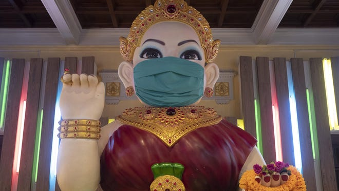 A giant statue of the Thai spiritual Nagkwank is dressed with a face mask at the Siam museum in Bangkok, Thailand, Friday, May 29, 2020. Nagkwank is a benevolent spirit who is deemed to bring luck and prosperity. She is the patron deity of all merchants and salesmen and can be seen in very many business establishments in Thailand. Thai authorities allowed museum and other businesses to reopen, selectively easing restrictions against the coronavirus.