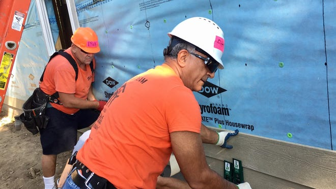 Ahmed Deldar, foreground, is a retired Lilly research scientist who volunteers frequently on Habitat for Humanity home-builds, like this one Tuesday near 38th Street and Capitol Avenue.