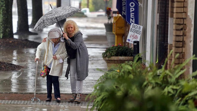 From left, Nancy Brewer and Diane Burleyson brave the rain for an outing in uptown Shelby on Thursday.