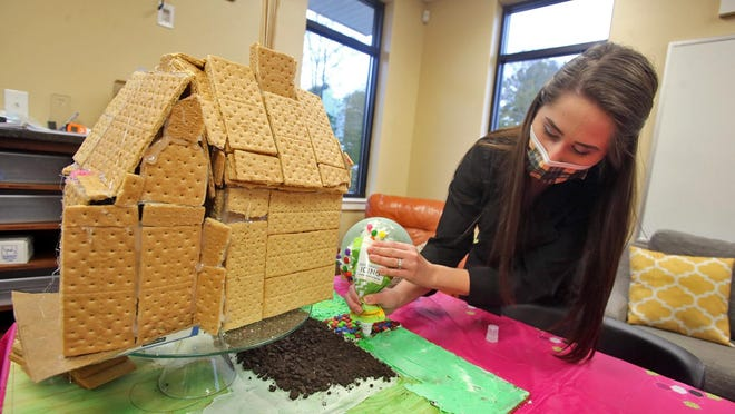 Amber Tesseneer adds grass icing around an Up inspired gingerbread house at Shelby Dental Care Center on Monday.