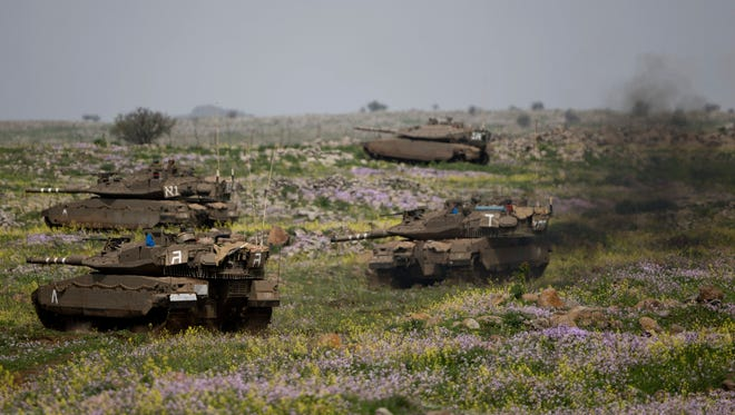 Israeli tanks take positions during training in the Israeli-controlled Golan Heights, near the border with Syria, on March 9.