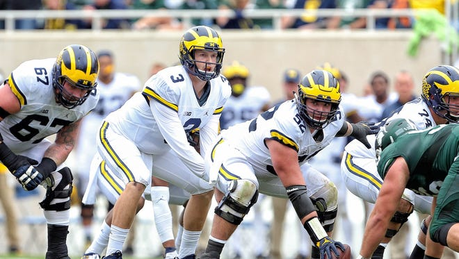 Michigan offensive lineman Mason Cole preparing to snap the ball to Wilton Speight in 2016 against Michigan State.