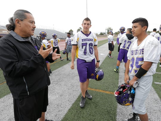EPISD interpreter Kenneth Kurita Jr., left, talks with Burges High School defensive end Jerry Molina, center, and George Frias who are two of three players at the school who are hearing impaired.