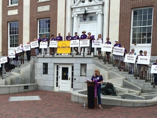 While Mission Speaker Nancy Bercaw addresses the Longest Day crowd, caregivers stand on the steps of City Hall and display signs listing daily caregiving tasks.