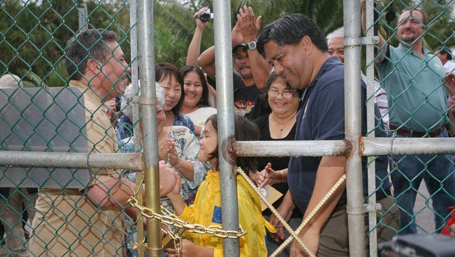 In this Aug. 31, 2011, file photo, Ordot resident Carina McCarthy, front center, and Gov. Eddie Calvo smile after locking the Ordot dump's main gate as Chalan Pago-Ordot Mayor Jessy Gogue, front right, and others watch.