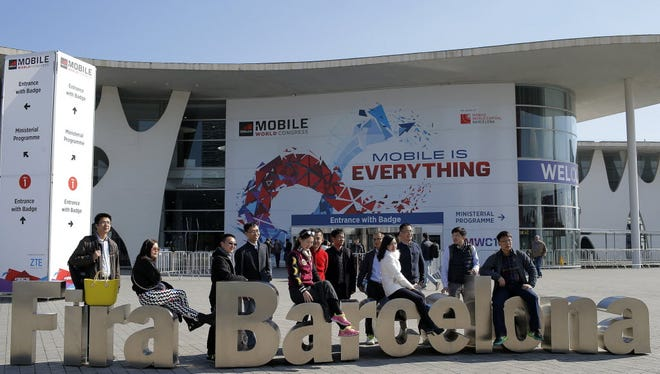 People take a picture in front of the venue of the Mobile World Congress, the world's largest mobile phone trade show in Barcelona, Spain, Friday, Feb. 19, 2016. The Mobile World Congress will be held on Feb. 22-25.