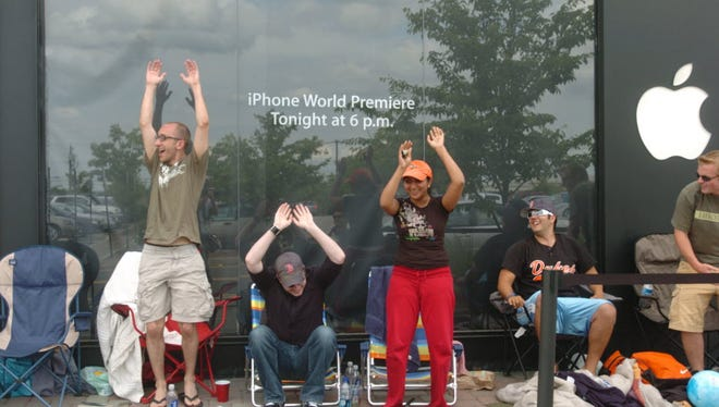 An impromptu wave begins at the start of the line for Apple's iPhone on 6/29/2007 in front of the Tice's corner Apple Store. About 10 people waited over night while line grew to over a hundred people in the early afternoon. The store opened its doors at 6pm.
