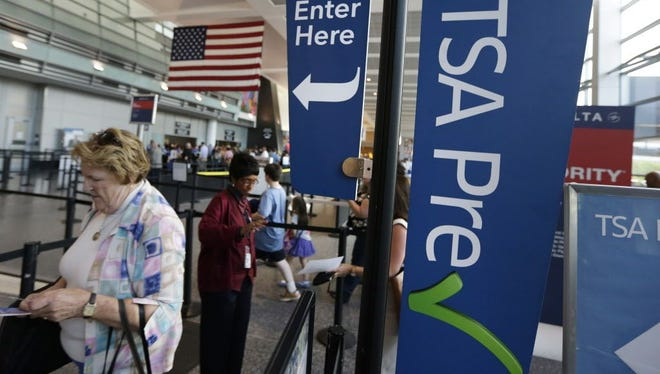 Travelers pass a sign for the Transportation Security Administration's TSA Precheck line as they walk to their departure gate in Terminal A at Logan International Airport on June 27, 2016, in Boston.