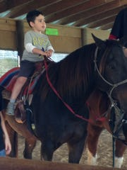 Dylan rides a horse at DnD Farm in Maurice last weekend.
