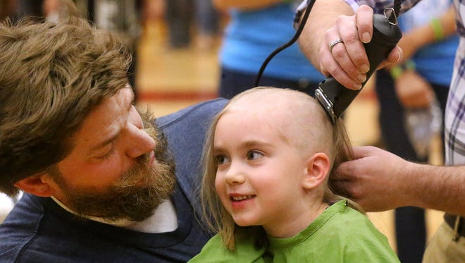 """Riverdale teacher Michael Shirley holds his daughter Mahayla Shirley, 6, as she shaves her head during Riverdale's 4th annual St. Baldrick's Event """"Brave the Shave"""" Event on Friday, March 17, by James Davis from Hair Five-0. Mahayla Shirley raised $1,580 dollars to fight childhood cancer."""