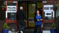 A man arrives to vote and a woman smiles after voting