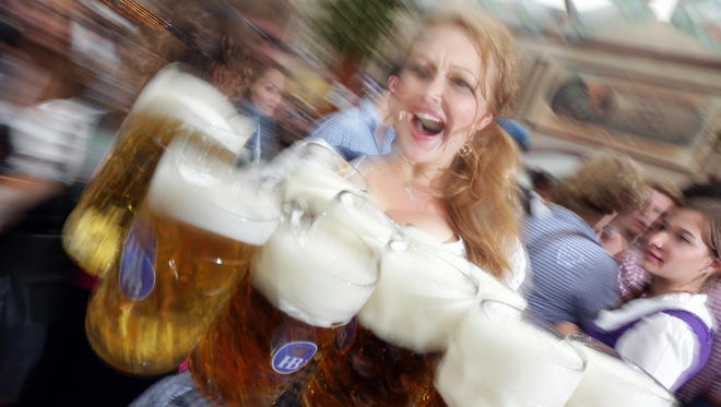 """A waitress carries beer mugs during the opening ceremony in the """"Hofbraeuzelt' beer tent of the Bavarian """"Oktoberfest"""" beer festival in Munich. Port Huron's Oktoberfest will be Oct. 21 at McMorran Place."""