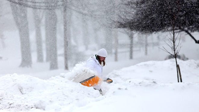 Emily Saunter shovels her driveway Monday during a massive snowstorm.