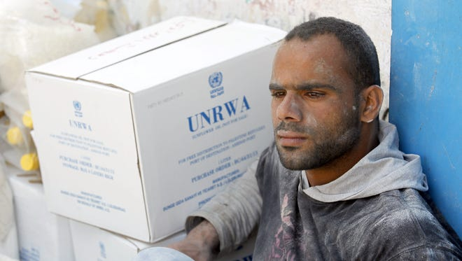 A Palestinian man covered in flour sits next to boxes as refugees receive humanitarian aid at the United Nations aid distribution centre in the Palestinian refugee camp of Rafah in the southern Gaza Strip on on October 6 ,2013. The United Nations Relief and Works Agency for Palestine Refugees (UNRWA) has removed food aid for 9,558 families in Gaza since the beginning of the year, while adding only 5,430 new families to the programme. AFP PHOTO/ SAID KHATIBSAID KHATIB/AFP/Getty Images ORIG FILE ID: 523560358