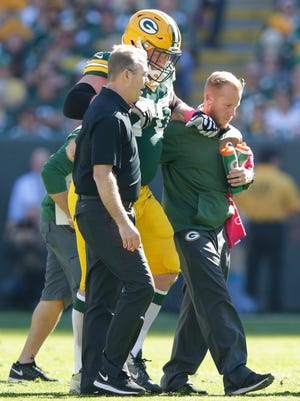 Green Bay Packers guard T.J. Lang (70) is helped off the field in the second quarter against St. Louis Rams at Lambeau Field.