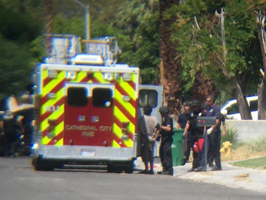 Paramedics check a suspect after he surrendered to