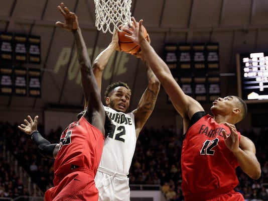 FILE - In this Nov. 18, 2017, file photo, Purdue forward Vince Edwards, center, pulls down a rebound between Fairfield defenders Ferron Flavors Jr., left, and Kevin Senghore-Peterson in the second half of an NCAA college basketball game in West Lafayette, Ind. All the competition, the jawing, the instruction and the good-natured ribbing from his parents and siblings taught Edwards a lot about the game and helped him round into one of the most versatile players in the nation. (AP Photo/AJ Mast, File)