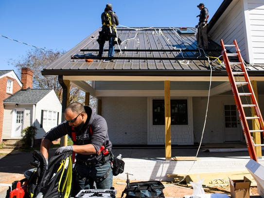 Jason Hernandez of Summit Solar grabs tools as he and other workers install solar panels on the roof of a home on Thursday, March 15, 2018.