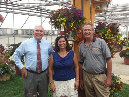 """New Jersey Department of Agriculture, Alfred W. Murray, assistant secretary, Laura DePrado, of Final Touch Plantscaping, and Kube Pak Family Owner, Rob Swanekamp, in one of the many display """"Gardens"""" at Kube Pak Open House, Sept. 30, in Allentown.   Kube Pak is a wholesale grower of fine garden plants, custom grown plugs, rooted cuttings and finished annuals and perennials.  The Open House is a massive, indoor display of thousands of mums, pansies (violas), carnations, (dianthus), as far as the eye could see.  A cornucopia of the best this fall season has to offer in flowers and flower combinations in every direction vertically and horizontally that drew buyers more than 200 landscapers and garden center operators who sell to their clients from Washington, D.C. to Pittsburgh, and up to Boston.  """"The Horticultural Industry in New Jersey is the State's largest Agriculture sector with 42 percent gross sales.  This includes nursery, sod, horticulture and floriculture,"""" according to New Jersey Department of Agriculture, Alfred Murray, Assistant Secretary."""