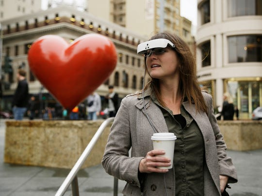 In this photo taken Thursday, Feb. 2, 2017, Yvonne Felix wears eSight electronic glasses and looks around Union Square during a visit to San Francisco. The glasses enable the legally blind to see. Felix was diagnosed with Stargardt's disease after being hit by a car at the age of seven.