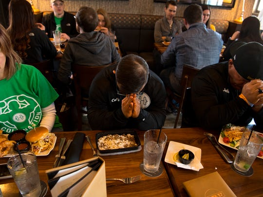 A pre-meal prayer at Bru Burger in Evansville kicks off a lunch of steamed white rice and lean beaf – the combined meal weighing-in at exactly three ounces – for Collin Clarke with his final bodybuilding competition coming up in a few hours. His mom, Jodie Clarke, left, went with the onion rings and burger while his coach, Jeff Kosor, did the grilled chicken salad. Collin could barely wait until he could have a real meal later that night.