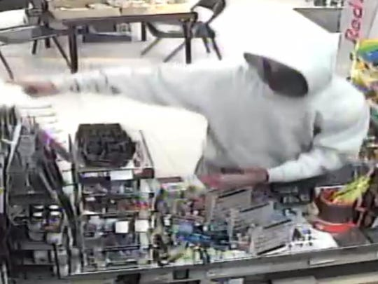 This surveillance image shows a man with a knife robbing