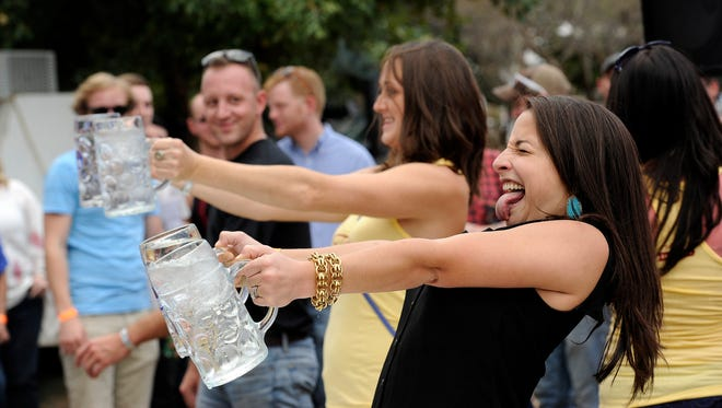 "Megan Charowski (right) makes a face as she tries to hold up a pair of beer steins in the ""stein hoist"" competition during the 2015 Abilene Beer Summit at Frontier Texas! The event returns there this weekend."
