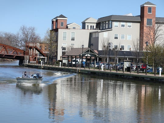 A lone boater glides through the village of Fairport on the opening day of the Erie Canal for boat traffic Wednesday, April 27, 2016.
