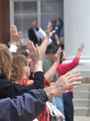 Participants in the local observance of the National Day of Prayer May 4 raise their hands at the close of the event.