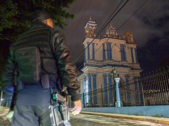 Un policía observa la fachada de una iglesia en San