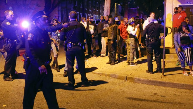 Police work to keep order among a crowd after two people were shot on the 600 block of W. 6th St. in Wilmington April 28, 2015.