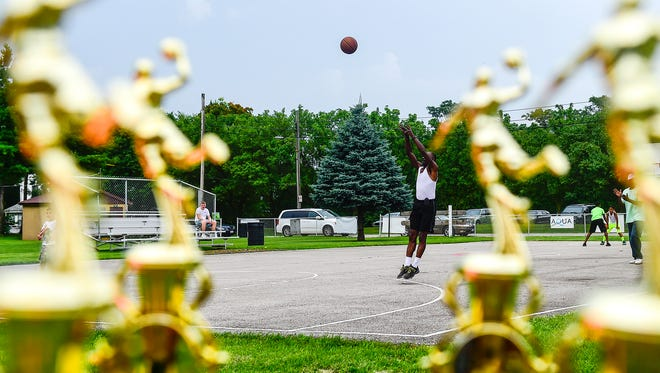 Ronald Miles takes a shot at the hoop while playing around on Martin Luther King Jr. Park basketball court during the opening ceremonies for the Mayes Basketball Tournament last year. At least 10 teams will play a double elimination tournament at the park this weekend.