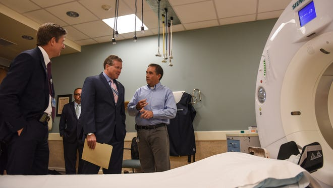 Rep. Charlie Dent, center, listens to Corey Hartman, chief of technology at the Penn State Hershey Medical Center, right, and Dr. Timothy Mosher, chairman of the department of radiology, left, talk about the CT scan during a visit to the Penn State Hershey Medical Center on Tuesday, Aug. 23, 2016. The hospital also recognized the congressman for his continued support of medical imaging innovation and efforts to protect jobs and patient access to care. Dent's 15th District includes parts of Lebanon County.