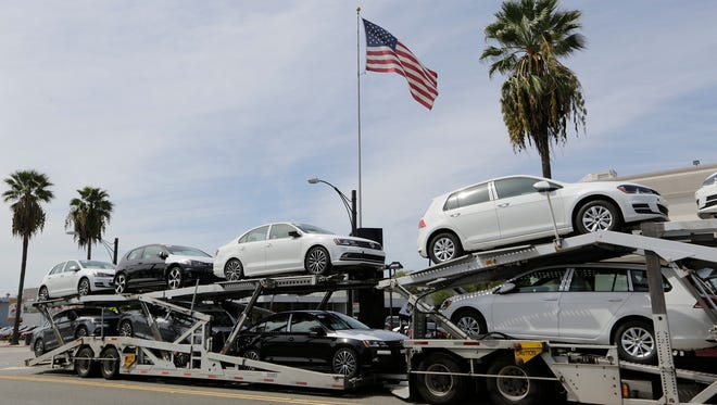 FILE - In this Sept. 21, 2015, file photo, a truck load of gasoline-engine Volkswagens is offloaded outside New Century Volkswagen dealership in Glendale, Calif. A federal judge in San Francisco is set to hear Friday, Dec. 16, 2016, whether Volkswagen, U.S. regulators and attorneys for car owners have reached a deal for the remaining 80,000 cars caught up in the company's emissions cheating scandal.