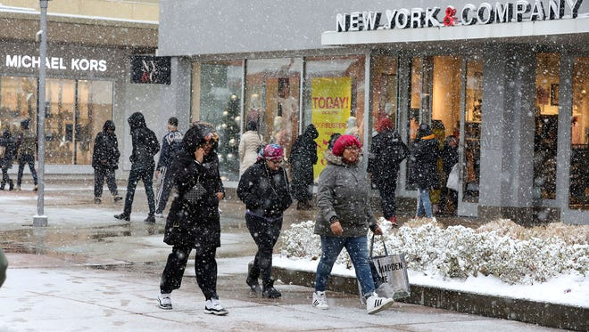 Shoppers brave the snow at the Cross County Shopping Center in Yonkers, N.Y., on Saturday, Dec. 9, 2017.