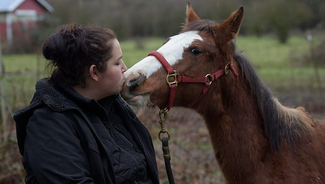 Tami Fawcett of Albany plays with a young mustang from Nevada at a ranch near Scio, Ore., Thursday Dec. 28, 2917. The horse was recently rescued by her nonprofit organization, Mustangs MEND, from being slaughtered.  (Mark Ylen/Albany Democrat-Herald via AP)