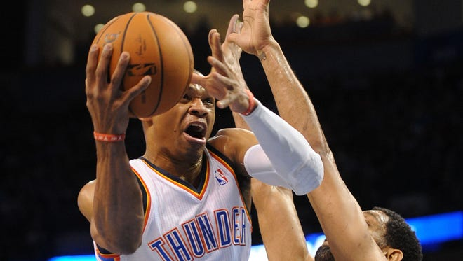 Oklahoma City Thunder guard Russell Westbrook (0) attacks the basket as San Antonio Spurs forward Tim Duncan (21) defends.