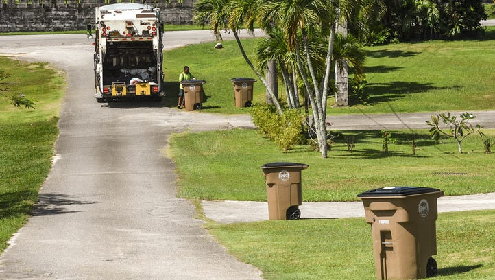 Guam Solid Waste Authority employees collect trash