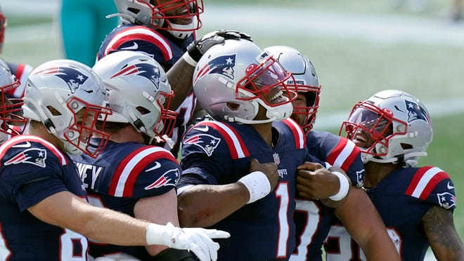 New England Patriots quarterback Cam Newton (1) celebrates his rushing touchdown against the Miami Dolphins with teammates in the first half of an NFL football game, Sunday, Sept. 13, 2020, in Foxborough, Mass.