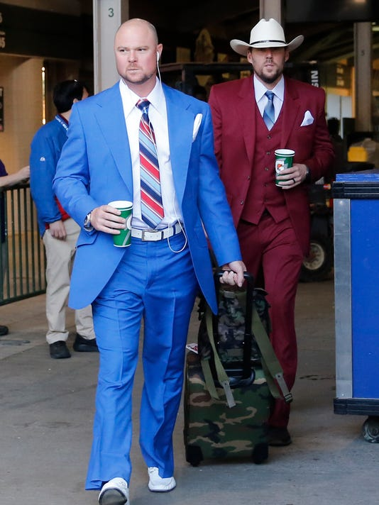 Chicago Cubs' Jon Lester, left, and John Lackey depart for the team's road trip wearing suits based on the character Ron Burgundy in the Anchor Man movie, after a baseball game against the San Francisco Giants Thursday, May 25, 2017, in Chicago. (AP Photo/Charles Rex Arbogast)