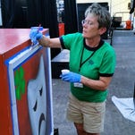 Susan Kloch Wendlandt of Marshfield paints one of the rolling prop carts used by the Wisconsin State 4-H Drama Company.