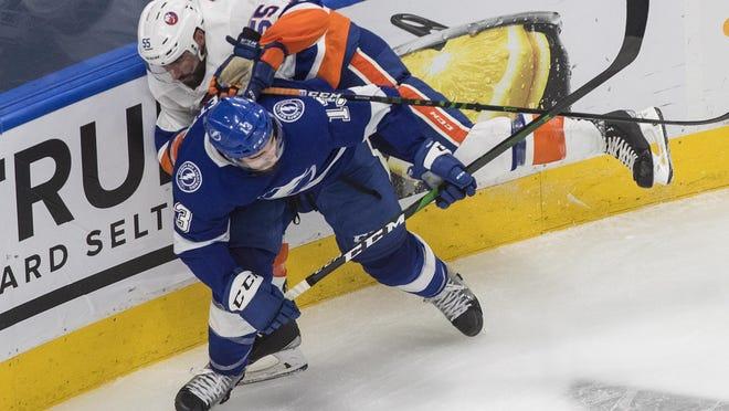 Tampa Bay Lightning center Cedric Paquette (13) and New York Islanders defenseman Johnny Boychuk (55) work along the boards Tuesday in Edmonton, Alberta.