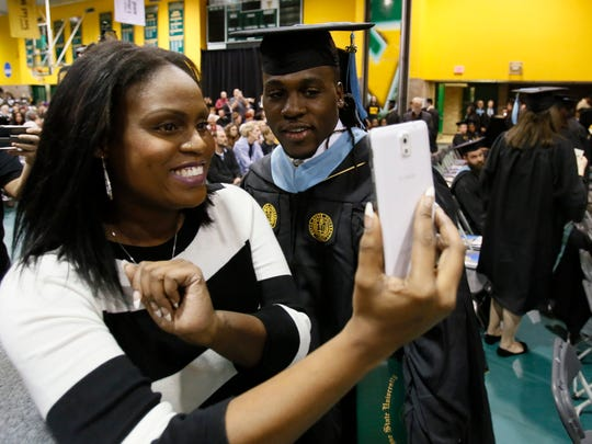 Ambie Bell Clayton takes a selfie with her brother, Lions running back Joique Bell, after he received his master's degree in sports administration from the College of Education at Wayne State  in Detroit on Saturday, Dec.10, 2016.