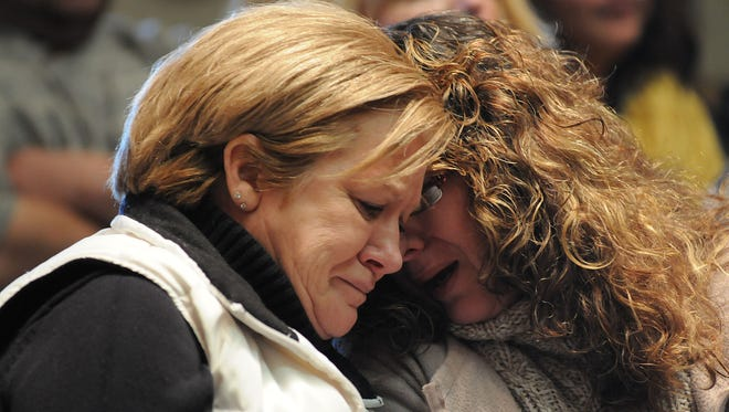Family and friends of the four murder victims of Donald Hoffman console one another during Hoffman's sentencing Wednesday morning.