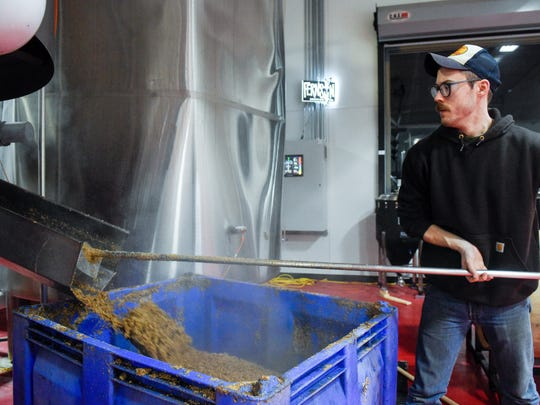 Fernson employee Kyle Larson shovels spent grain from