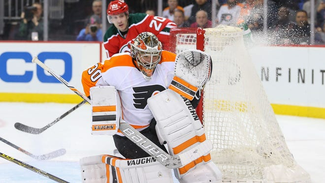 New Jersey Devils right wing Lee Stempniak (20) looks for the puck after a save by Philadelphia Flyers goalie Michal Neuvirth (30) during the second period at Prudential Center.