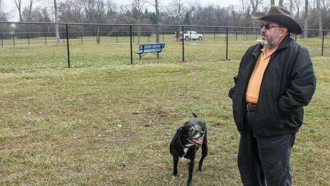 Dennis Ridolfi stands in the Livonia dog park with his dog, Patience. The dog park opened Monday and saw a few canines stop in to play.