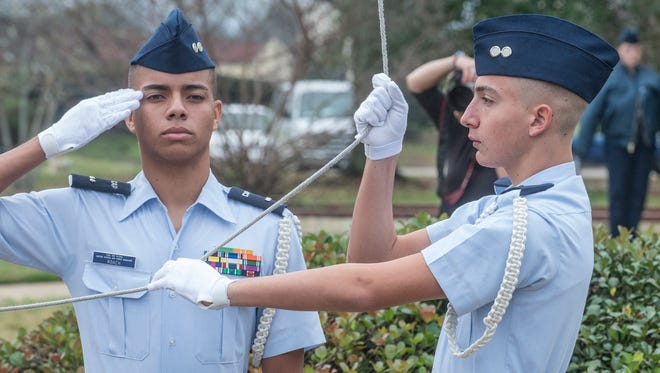 Cadet Cameron Roach of Deer Valley Composite Squadron 302 in Phoenix, Arizona, salutes while Jacob Madsen raises the flag. Civil Air Patrol cadets from across America compete at Maxwell Air Force Base on Thursday, Dec. 31, 2015, for the 2015 National Cadet Competition, renewing a prestigious CAP inspection and drill event that originated nearly 70 years ago.